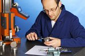 Young male engineer in blue overall measuring a metal part with caliper, isolated on blue background.