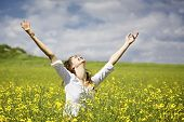 Young woman standing in yellow rapeseed field raising her arms expressing gratitude or freedom.