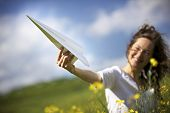 stock photo of lifting-off  - Jolly woman in green field holding up a paper plane into the blue sky expressing liberation - JPG