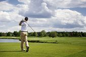 stock photo of cloud formation  - Male golf player teeing off golf ball from tee box - JPG