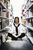 Female student sitting in Yoga pose in between bookshelves in modern university library and meditati