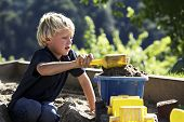 Young boy scooping sand onto toy truck in sandbox.