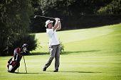Junge männliche Golfspieler pitching am Golfplatz mit Golf Tasche beiseite.