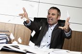 Overloaded senior businessman being upset about work, tearing papers and screaming, sitting at offic
