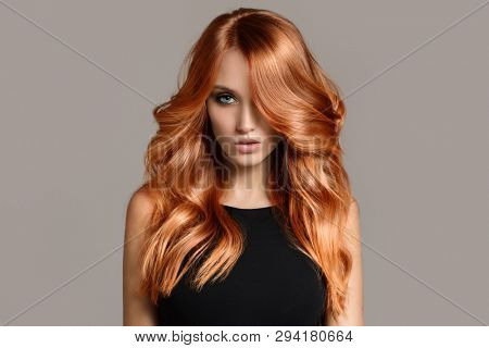 poster of Beautiful woman with long wavy coloring hair. Flat gray background.
