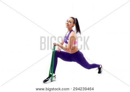 poster of Beautiful Young  Woman Doing Lunge Exercisewith Sport Fitness Rubber Bands  In Fitness Gym Isolated