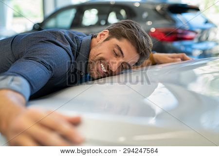 poster of Happy young man hugging his new car in showroom. Satisfied guy with closed eyes embracing the hood o