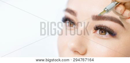 poster of Beautiful Young Girl With Long Eyelashes Tweezing Her Eyebrows In A Beauty Salon. Eyebrow Correction