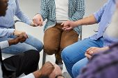 High Angle Close Up Of People Holding Hands Sitting In Circle During Therapy Session In Support Grou poster