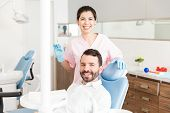 Portrait Of Male Patient And Female Dermatologist Smiling During Procedure poster