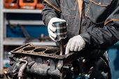 Car Mechanic Holding A New Piston For The Engine, Overhaul.. Engine On A Repair Stand With Piston An poster