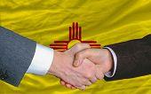 Delante de la bandera del Estado americano de apretón de manos de dos hombres de negocios nuevo México después de mucho