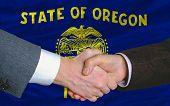 Delante de la bandera del estado estadounidense de Oregon dos empresarios apretón de manos después de mucho