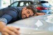 Happy young man hugging his new car in showroom. Satisfied guy with closed eyes embracing the hood o poster