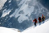 Team of three alpinists descending a mountain