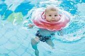Cute Little Baby Child Learning To Swim With Swimming Ring In An Indoor Pool. Newborn Girl Or Boy Ha poster