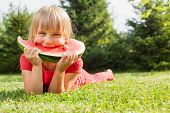 Portrait of happy elementary age girl enjoying eating slice of juicy watermelon lying on a meadow in poster