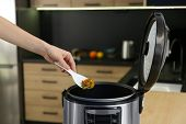 Young Woman Preparing Food With Modern Multi Cooker In Kitchen poster