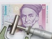 stock photo of micrometer  - Measuring a bolt of ten millimeter with a micrometer. Lying on a ten Deutsche Mark bank note. - JPG