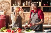 Senior Couple Having Fun On Kitchen. Playful Woman Making Faces With Pepper Slices, Free Space poster
