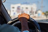Driver In Car Holding Steering Wheel. Blurred Building. North Arica, Tunisia