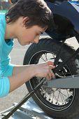 Teenage boy repairing motorcycle