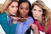Three attractive women blowing kisses