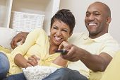 A happy African American man and woman couple in their thirties sitting at home, eating popcorn and