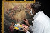 Restorer Working On Oil Painting Canvas