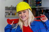 junger Mechaniker mit gelben Helm und Schraubenschlüssel in einem Workshop. seltene weibliche Berufe.
