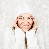 Smiling young woman in white on snow background
