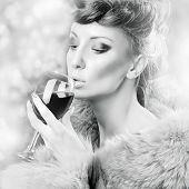 Glamorous woman in fur drinking wine
