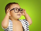 Portrait Of Baby Boy Wearing Eyeglasses against a green background