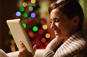 Smiling Young Woman Using Tablet Pc In Front Of Christmas Tree