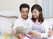 stock photo of snuggle  - young asian couple looking at tablet computer on couch - JPG