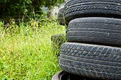 Old Road Tires Stacked On Grass Land.