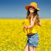 young woman on blooming rapeseed field in summer