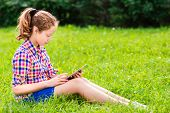 Beautiful Teenager Girl In Casual Clothes Sitting On The Grass With Digital Tablet On Her Knees