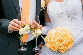 Hands Of Bride And Groom Holding Wedding Bouquet And Glasses