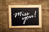 stock photo of miss you  - Miss you note on black message board - JPG