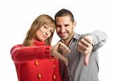 Couple With Their Thumbs Down Over White Background