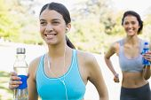 Smiling young fit women with water bottle listening music while jogging in park