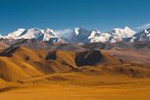 stock photo of nepali  - Peaks of the himalayas poke through the beautiful natural landscape of the barren mountainous terrain at the himalayan border between Nepal and Tibet - JPG