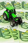a tractor standing on euro banknotes. symbolic photo for costs, revenues and subsidies a farmer in a