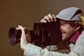 A Man Wearing A Cap With An Old Movie Camera