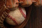Old leather baseball glove with weathered baseball on wood background.  Highly detailed closeup take