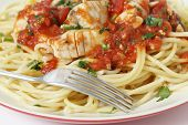 Fresh fish in arrabbiata sauce, served on spaghetti and with a fork, sprinkled with a parsely garnis