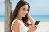Portrait Of A Beautiful Young Woman At Beach Looking At Cellphone