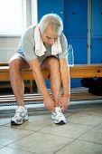 Senior man tying up sneakers in fitness club locker room