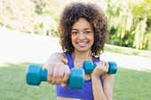 Portrait of happy young woman lifting free weights in park